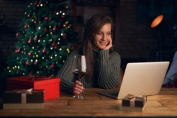Woman drinking wine, using laptop, shopping online. Christmas tree in the background.