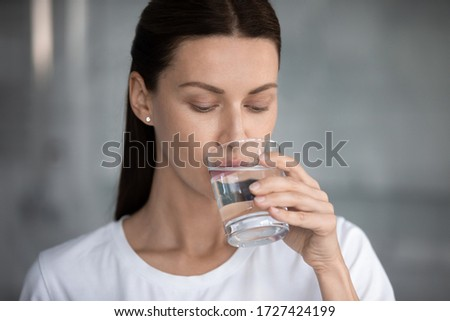 Woman drinks still water close up portrait. Quench thirst, water balance and weight control, caring of skin and body, hangover relief, body refreshment, energy recovery, dehydration prevention concept