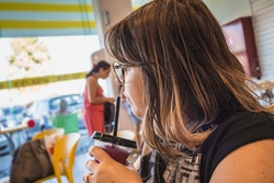 Woman drinks sweet shaved ice and looks away at ice cream parlor
