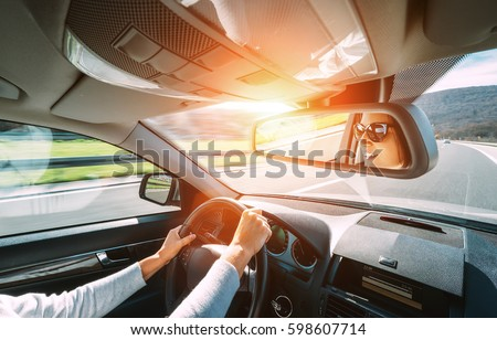 Woman drive a car reflects in back view mirror