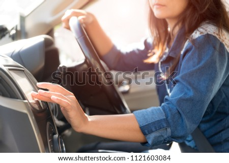 woman driver hand touching the screen entering an address into the navigation system and turning on car radio system.
