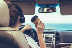 Woman driver in the headphones driving a car. Girl relaxing in auto trip drinking coffee paper cup traveling along ocean tropical beach in background. Traveler concept.