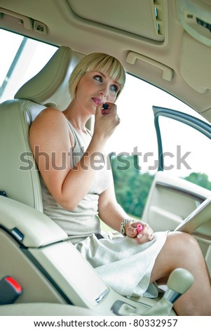 woman driver looking in rear view mirror and putting some lipstick in the car stock photo. Black Bedroom Furniture Sets. Home Design Ideas
