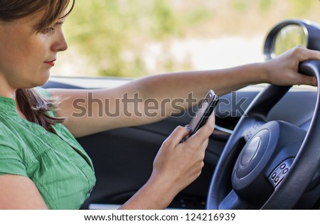 Woman driver reading a text message on a mobile
