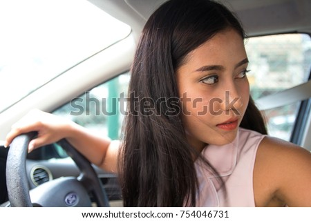 Woman driving a car - female fresh driver at car wheel, looking behind going reverse. young girl new driver parking car, ride a car backward. trying to drive reverse turning back. checks the backseat.