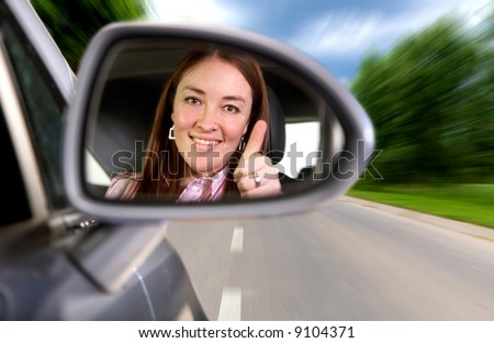 woman driving a car on a road with thumbs up in the mirror