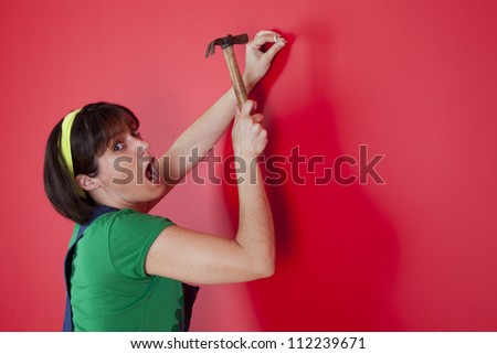 woman driving a nail in a red wall