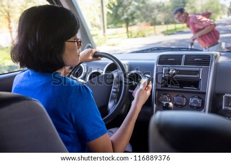 Woman driving and texting on cell phone, about to hit a man on a bicycle.