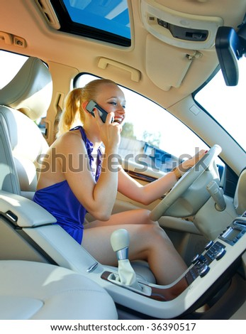 woman driving car and talking on mobile phone