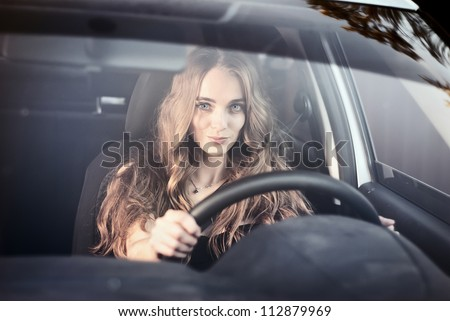 Woman driving car. Beautiful happy woman in car in the evening. Windshield view