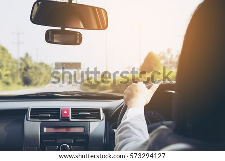 Woman driving car using two hand