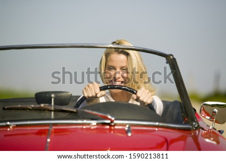 Woman driving convertible in countryside