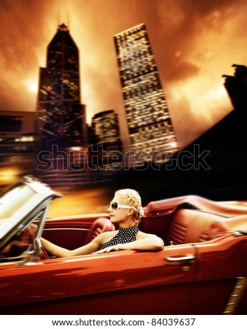 Woman driving retro car in modern city.