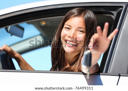 Woman driving showing car keys out the window. Young female driving happy about her new car or drivers license. Beautiful mixed race Caucasian / Asian driver. - stock photo