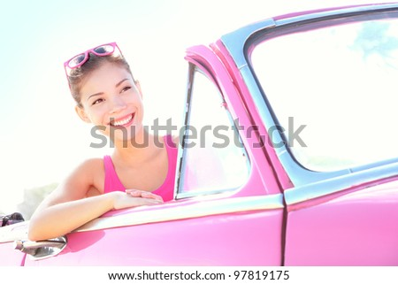Photo of Woman driving vintage car. Retro style image of happy smiling young woman in old pink car going on road trip on sunny spring or summer day. Beautiful multiracial Caucasian / Asian in Havana, Cuba.