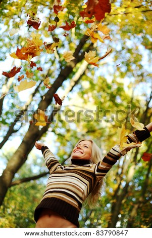 woman drop up leaves in autumn park