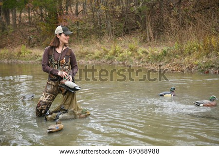 Woman Duck Hunter in Pond wearing Camo Waders
