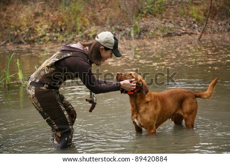 Woman Duck Hunter petting Labrador Retriever in Pond