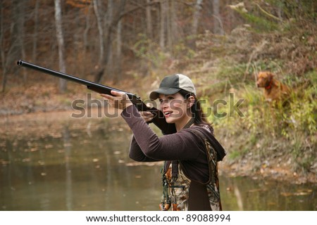 Woman Duck Hunter wearing Cap and Camo Waders Shooting Rifle in Pond with Dog in Background