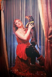Woman during a stylized theatrical circus photo shoot in a beautiful red location. Girl posing on stage with curtain
