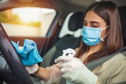 Woman during pandemic isolation at city, she is in car and disinfect. Woman in car disinfecting steering wheel. Adult Woman Disinfecting Car Dash Board with Antiseptic and Wet Wipe