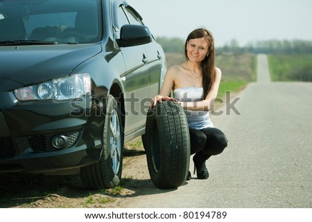 woman during the wheel changing at road