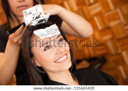 Woman dying her hair at the beauty salon