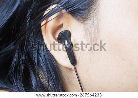 Woman ear with black earphone, Black earphone in girl\'s ear