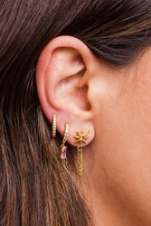 Woman ear with mulriple piercings wearing beautiful earrings with zirconia- details capture