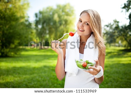Woman eat salad after exercise