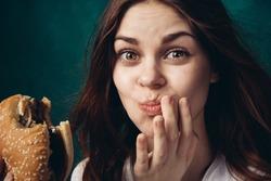 Woman eating a hamburger, chewing a hamburger, hamburger in hand