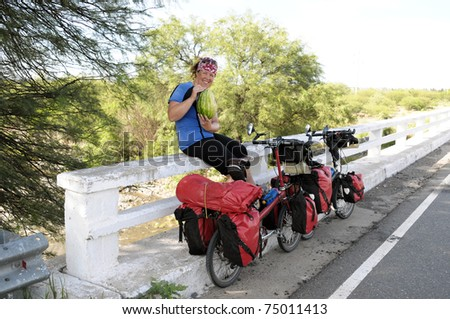 Woman eating a water melon on a side of a road