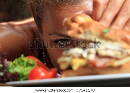 Woman eating a yummy cheeseburger