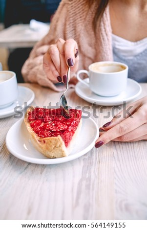 woman eating berry dessert with a spoon in a coffee shop and drinks cofee. female holds a saucer with a pie on a wooden table. focus on the cake. #564149155