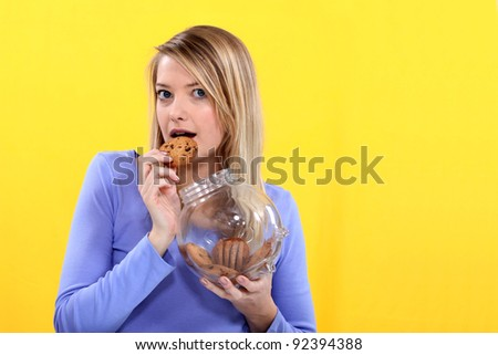 Woman eating biscuit from jar