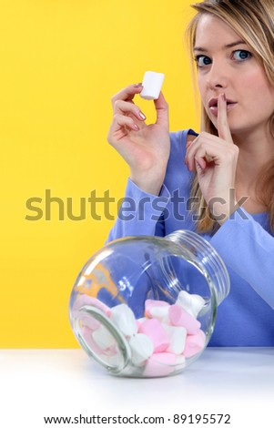 woman eating bonbons and making a silence sign - stock photo