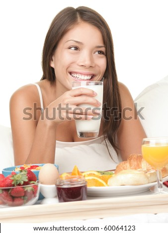 Woman eating breakfast in bed drinking a glass of milk. Morning photo of beautiful natural mixed race Chinese / White Caucasian female model smiling looking away