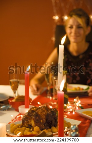 Woman eating candle lit dinner, selective focus