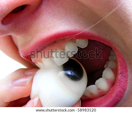 Woman eating candy like an eye - close up