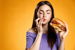 Woman eating cheeseburger with satisfaction. Girl enjoys tasty hamburger takeaway, licking fingers delicious bite of burger, order fastfood delivery while hungry, standing over orange background