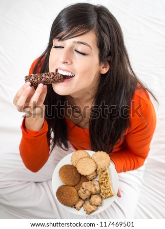 Woman eating chocolate bar. Hungry girl biting delicious  snack sitting on white bed indoor. Breaking diet concept. - stock photo