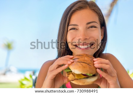 Woman eating fast food chicken burger at resort restaurant. Asian girl enjoying summer vacation at outdoor cafe with lunch meal, hamburger and fries.