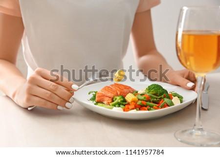 Woman eating fresh salad and fish at light table #1141957784