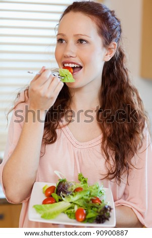 Woman eating fresh salad in the kitchen