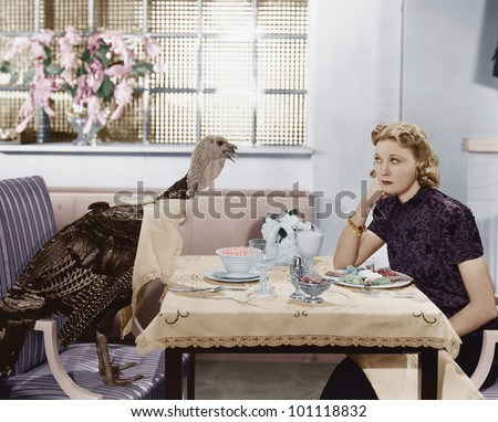 woman eating meal at table with ...