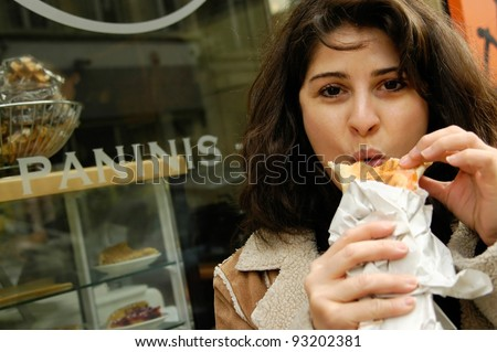 Woman eating panini at panini shop
