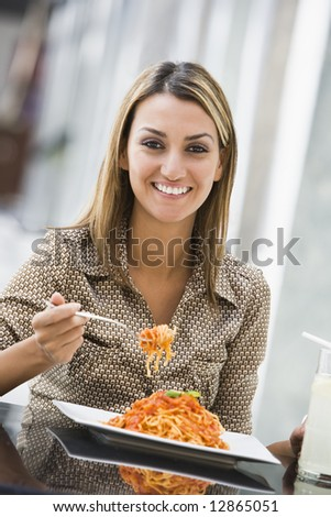 Woman eating plate of pasta at cafe