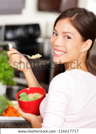 Woman eating quinoa / broccoli salad. Eat healthy food lifestyle concept with beautiful young multiracial woman in her kitchen. - stock photo