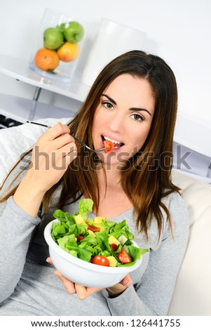 Woman eating salad. Beautiful healthy smiling Caucasian woman enjoying a fresh healthy salad sitting in sofa looking up. High angle view with copy space on modern interior.