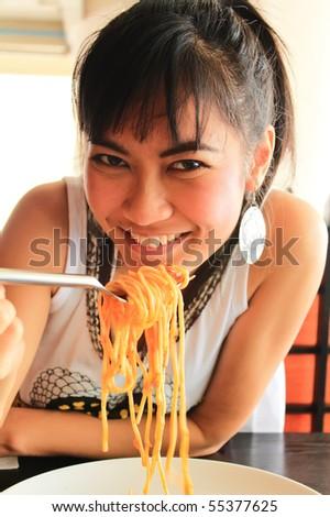 woman eating spaghetti in restaurant